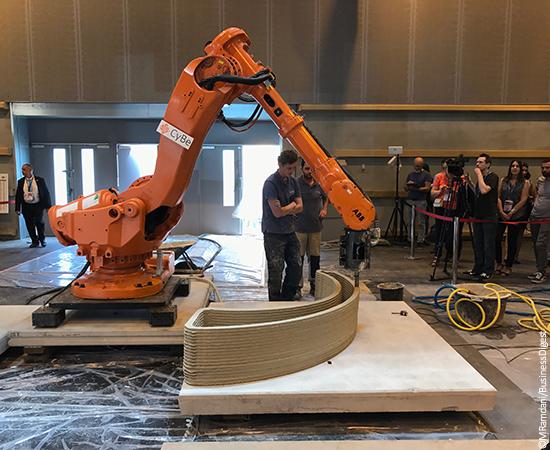 """Ici, """"l'imprimante 3D"""" de Bouygues Construction dépose successivement des fines couches de béton pour monter un élément de mobilier urbain."""
